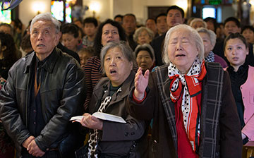 Shen Lu de (right foreground) joins with fellow worshippers to sing a hymn at Chongwenmen Church in Beijing, China. The church was established in 1870 by U.S. Methodists. Then known as Asbury Church, it was burned down during the Boxer Rebellion in 1900 and rebuilt in 1904. A UMNS photo by Mike DuBose. Accompanies UMNS story # 181. 6/10/13.